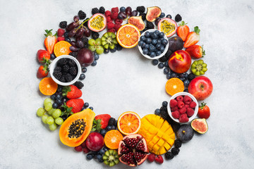 Wall Mural - Frame made of healthy raw rainbow fruits, mango papaya strawberries oranges passion fruits berries on oval serving plate on light concrete background, top view, copy space, selective focus