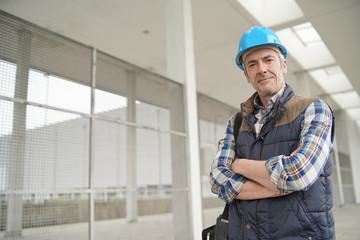 Construction worker looking at camera outside contemporary building