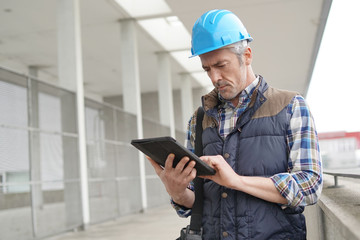 Lead architect checking tablet outside contemporary building