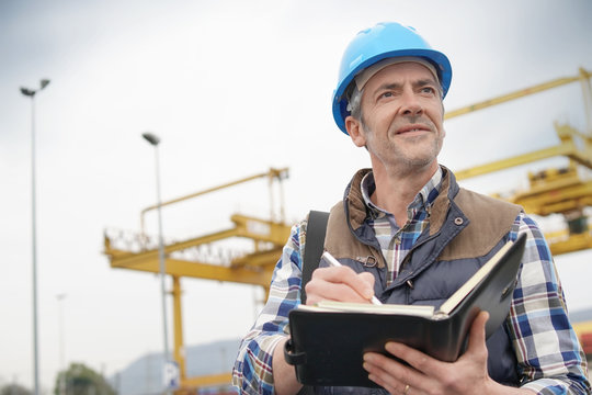 Mature construction worker inspecting work sight with notebook