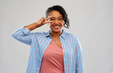 people and gesture concept - happy african american young woman showing peace hand sign over pink background