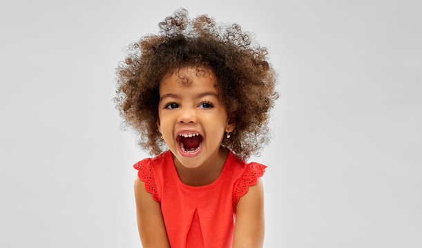 emotion, childhood and expression concept - happy laughing little african american girl over grey background