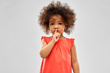 childhood and people concept - little african american girl making shush gesture over grey background Wall mural