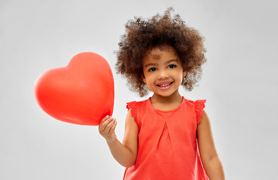 childhood and people concept - happy little african american girl with red heart shaped balloon over grey background