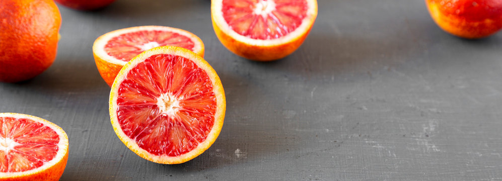 Whole and halved blood oranges on black surface, side view. Copy space.