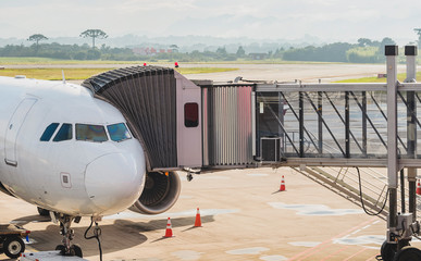 Jetway connected to the airplane for boarding passengers. Boarding bridge.