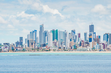 Seafront city. Touristic city with a beach, banks of corals on the sea at low tide and tall buildings on background. Praia do Bessa beach at the city of Joao Pessoa.
