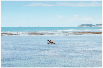 In the middle of sea, tourists kayaking between banks of corals on low tide 0.0 of Caribessa, Bessa beach (praia do Bessa). Touristic destination.