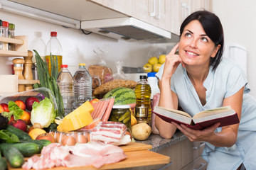 Female is searching recipe of meat in special book on the kitchen