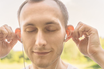 The man in the headphones holds his ears