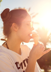 Girl in sunglasses licking yellow icecream in sunlight