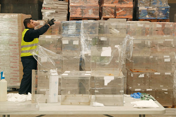 A worker moves ballot boxes as they are to be taken from a warehouse and sent to polling stations in Barcelona
