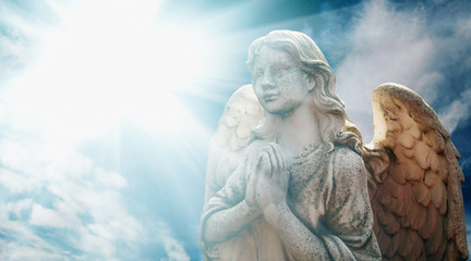 Antique statue of wonderful angel in the rays of light.