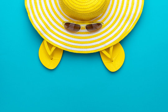 top view of yellow sunglasses, striped retro hat and flip-flops