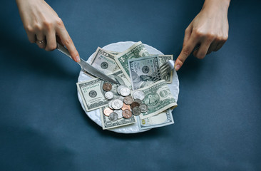 Money lying on the plate with fork and knife. Dollars photo. Greedy corruption concept. Bribe idea. Person eating banknotes. Dimes and cents coins.
