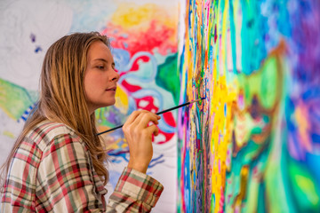Joyful young female artist painting on the wall, using brush and bright acrylic paints Wall mural