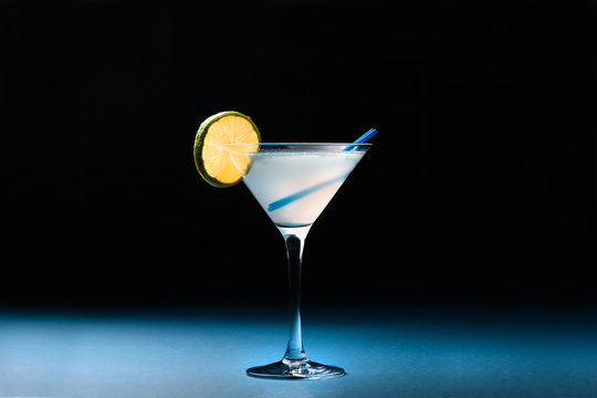 Classic Daiquiri cocktail with lime in martini glass on a dark blue background. Space for text.