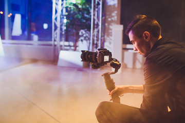 Professional videographer holding camera on 3-axis gimbal. Videographer using steadicam. Pro equipment helps to make high quality video without shaking.