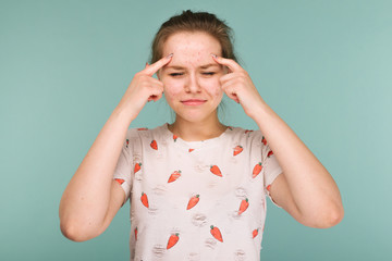 Portrait of teen girl touching her face and looking for acne