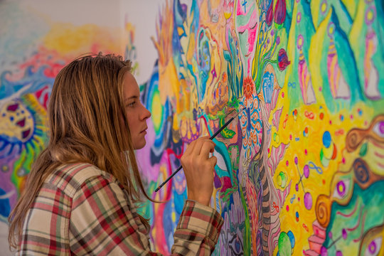Concentrated young woman coloring her bedroom wall in psychedelic mind flow style, art therapy concept