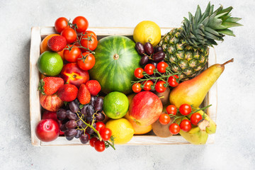 Wall Mural - Healthy raw rainbow fruits, mango papaya strawberries limes watermelon pineapple tomatoes in white box on light concrete background, top view, selective focus