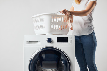 Partial view of woman with landry basket and washing machine isolated on grey