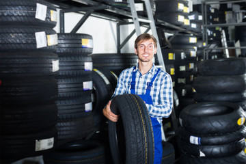 young happy mechanic man working with car tires in workshop