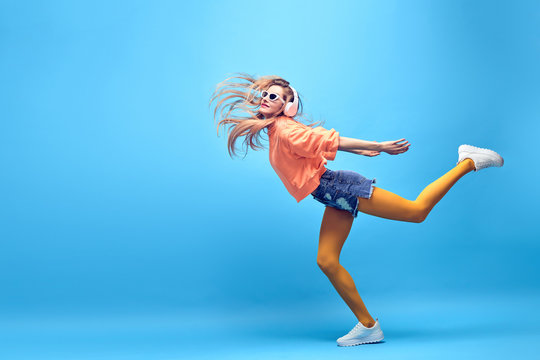 Young easy-going happy hipster Woman dance Having Fun in Stylish fashion headphones. Beautiful excited Girl laughing enjoy music in summer Trendy outfit. Creative art dancing fashionable concept