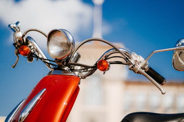 Closeup chrome detail and headlamp of orange retro vintage scooter under blue sky and sun in front of defocused tower