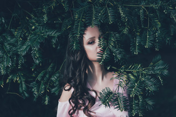 Covered face with a plant, cute woman in the thicket of the forest