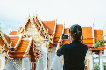 Asian woman travelers from behind taking ancient temple buildings photos in the ancient temple scene background with copy space- Bangkok- Thailand
