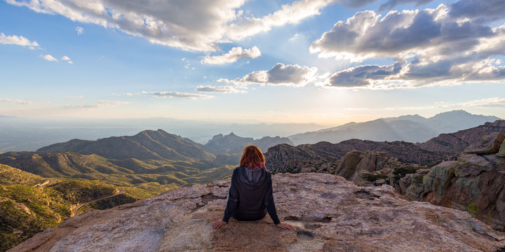A woman staring down from the top of Mount Lemmon in Arizona while the sun starts to set.