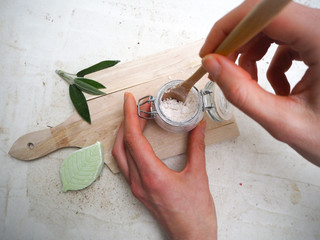 Caucasian woman making homemade vegan deodorant in a glass jar and adhering to a zero waste and plastic free lifestyle