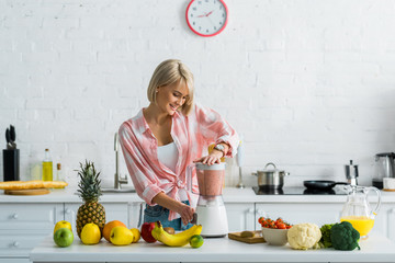 happy young woman preparing tasty nutritious smoothie in blender