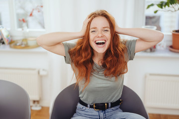 Cute young woman laughing at a hilarious joke