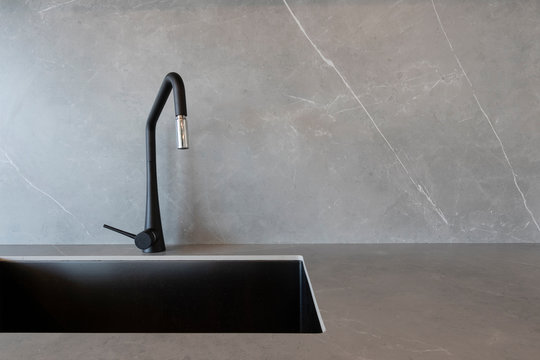 A black sink and a matt-finish black faucet set against grey surfaces made of porcelain slabs that mimic the look of natural stones