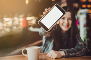 blurry portrait of a happy smiling brunette girl who holds a mobile phone with a clean screen ready for your logo or text..