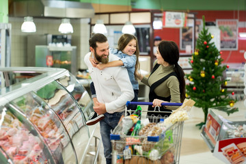 Young family with a little girl shopping in a large supermarket. Concept of a new year.
