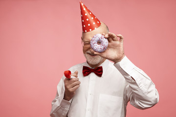 Fun, joy, celebration and holiday concept. Joyful positive mature retired male wearing red cone hat, bow tie, white shirt and spectacles relaxing at birthday party, holding doughnut and whistle
