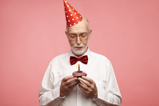 Age, senior people, birthday and celebration concept. Isolated portrait of handsome unshaven elderly man celebrating his seventieth anniversary holding cupcake, going to make wish, blowing