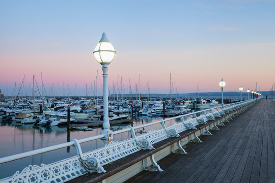 A wooden pier at sunset looking over the marina at the sailboats and yachts