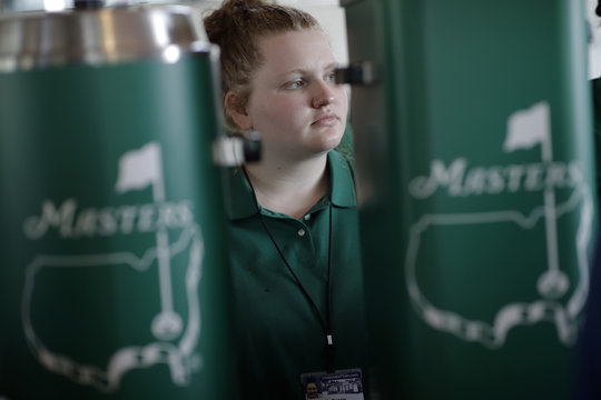 A concession stand worker is shown between Masters logos during practice for the 2019 Masters golf tournament at the Augusta National Golf Club in Augusta, Georgia, U.S.