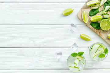 summer cocktails for freshness with lime, mint, cucumber and spinach and ice on white background top view mockup