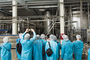 excursion at the factory. People in protection, shoe covers, blue overalls stand and listen to a tour of the metal brewery. People Photograph production on the phone Wall mural