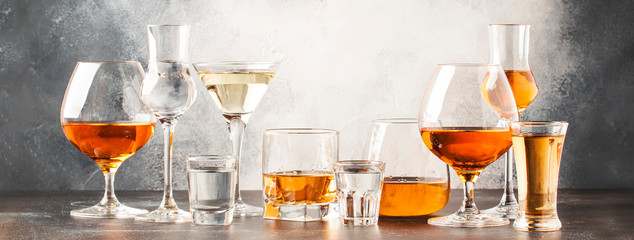 Photo sur Plexiglas Bar Set of hard strong alcoholic drinks and spirits in glasses in assortment: vodka, cognac, tequila, brandy and whiskey, grappa, liqueur, vermouth, tincture, rum. Gray bar counter background