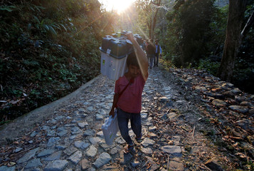 A porter carries a Voter Verifiable Paper Audit Trail machine and an Electronic Voting Machine through Buxa tiger reserve forest to a remote polling station, in Alipurduar district