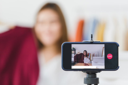 Beautiful asian woman blogger is showing clothes and dress. In front of the smartphone camera to recording vlog video live streaming at home.Business online influencer on social media concept.