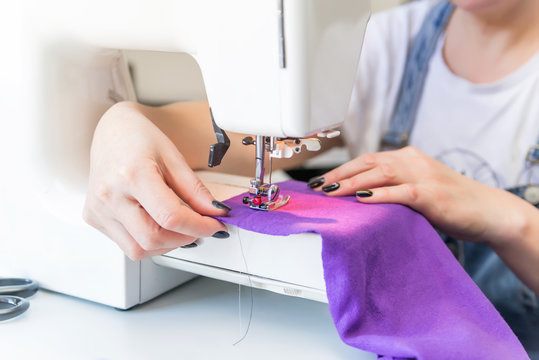 closeup  seamstress sitting and sews on sewing machine. Dressmaker work on the sewing machine. Tailor making a garment in her workplace. Hobby sewing as a small business concept
