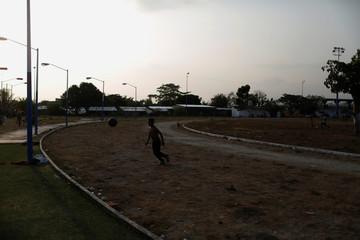A child kicks a ball at an improvised shelter in Mapastepec