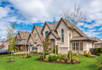 Beautiful exterior of newly built luxury home. Yard with green grass and walkway lead to front entrance. Fototapete